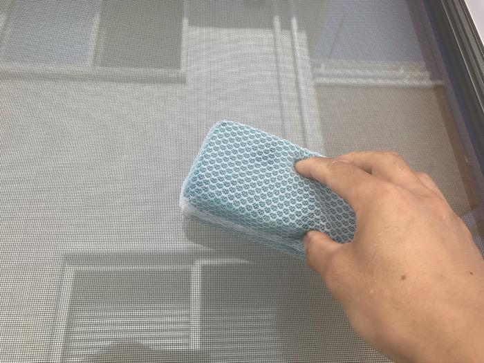水を含んだスポンジで窓を洗う