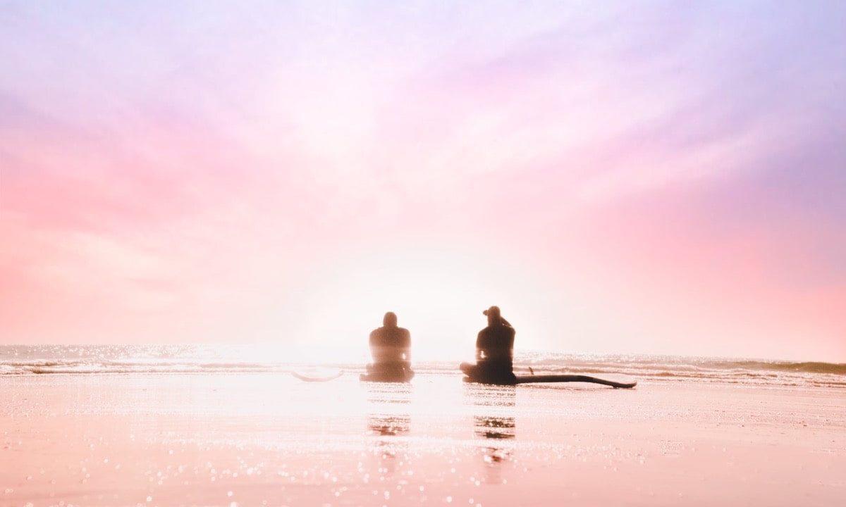 夜明けの海岸に座る男女
