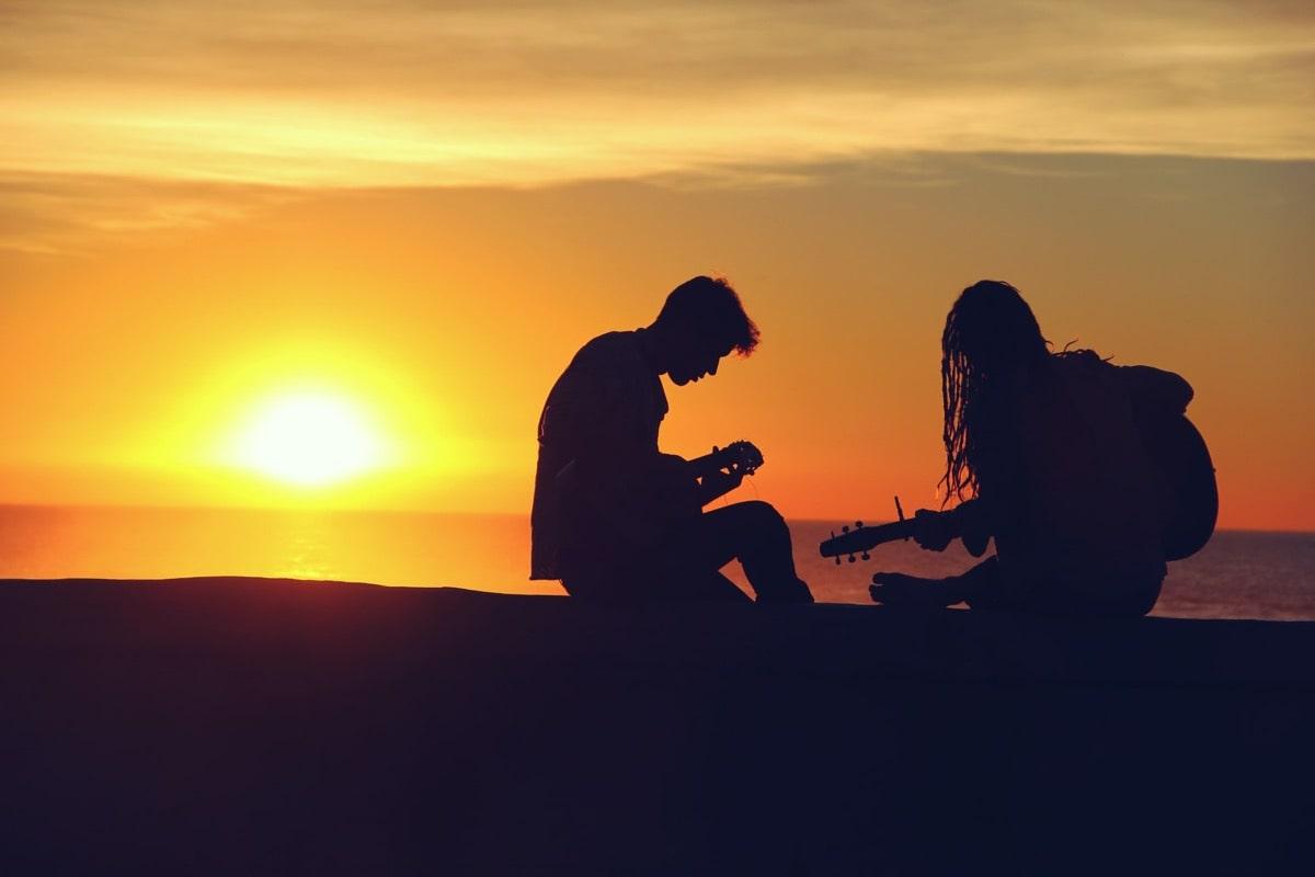 夕暮れにギターを持って歌う男女